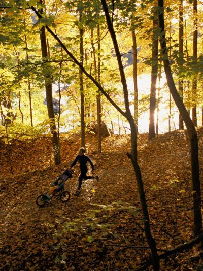 A Woman Pushes a Baby Stroller as She Jogs Through a Wooded Area-Skip Brown-Photographic Print