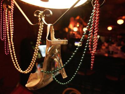 A Woman's High Heeled Shoe Hangs with Some Mardi Gras Beads--Photographic Print