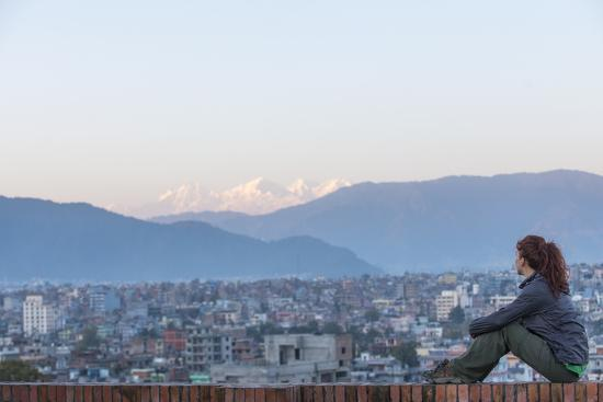 A Woman Sits on a Rooftop in Kathmandu and with the Ganesh Himal Mountain Range in the Distance-Alex Treadway-Photographic Print