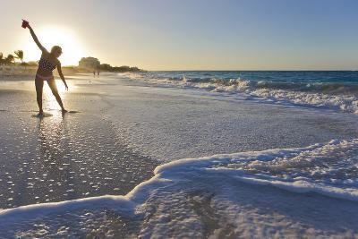 A Woman Standing in Front of the Sun Glows and Casts a Shadow on the Beach-Mike Theiss-Photographic Print