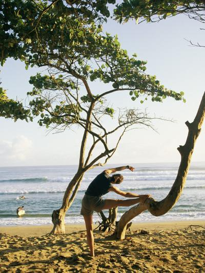 A Woman Stretches Her Body on a Small Tree at a Sandy Beach-Skip Brown-Photographic Print
