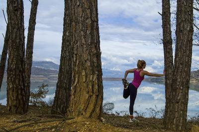 A Woman Stretching Among Large Pine Trees after a Run-Keith Ladzinski-Photographic Print
