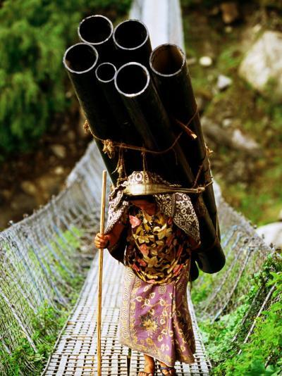 A Women Carrying a Heavy Load Across a Bridge, Kalopani, Annapurna Circuit, Nepal-Andrew Parkinson-Photographic Print