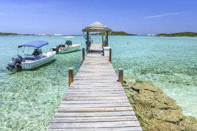 A Wood Pier Leads to Moored Boats and Clear Tropical Waters Near Staniel Cay, Exuma, Bahamas-James White-Photographic Print