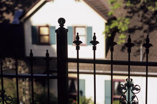 A Wrought Iron Black Fence Frames a Home with Blue Shuttered Windows-Paul Damien-Photographic Print