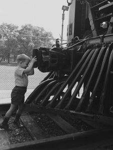 A Young Boy Standing in Front of a Locomotive