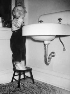 A Young Girl Brushes Her Teeth at the Sink, Ca. 1955