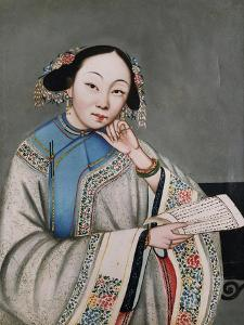 A Young Girl Seated in an Interior Reading an Album