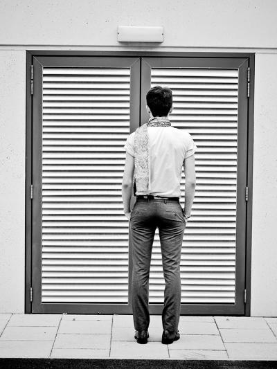 A Young Man Standing in the Street Looking at a Pair of Doors-India Hobson-Photographic Print