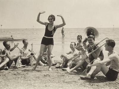 A Young Woman, Surrounded by Musicians, Dances on a Beach of the Lido of Venice--Photographic Print