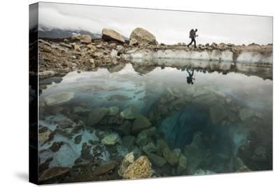 A Climber Hikes Near a Glacial Pool on Lower Ruth Glacier in Denali National Park