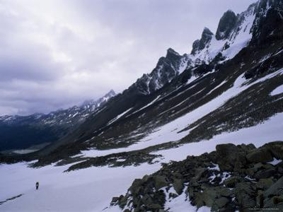 Backpacker Climbing Pass to Get to Glacier Grey, in the Torres Circuit, Chile, South America