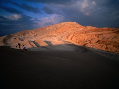 Couple of Hikers Walking Through Shadows at Dusk, Valle De La Luna, Chile