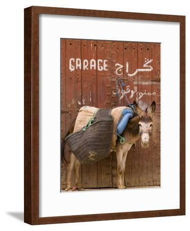 """Mule Parked in Front of a Sign That Reads """"Garage"""""""