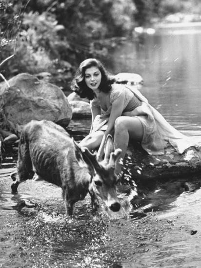 Actress Pier Angeli, Clad in Strapless Chiffon Party Dress Sitting on a Rock in a Pond-Allan Grant-Premium Photographic Print