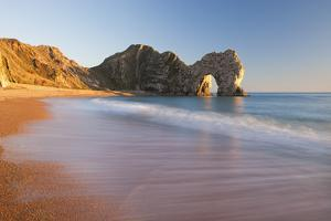 Waves Sweeping onto the Deserted Beach at Durdle Door, Dorset, England. Winter by Adam Burton