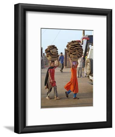 Two Young Indian Girls Carry Baskets of Animal Dung on their Heads