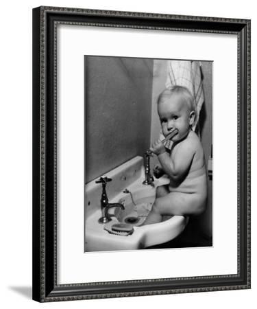 Adorable Baby Brushing Teeth While Sitting in Sink--Framed Premium Photographic Print