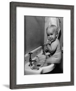 Adorable Baby Brushing Teeth While Sitting in Sink