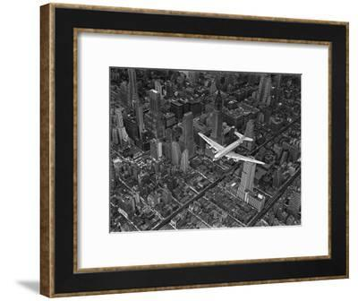 Aerial View of a Dc-4 Passenger Plane in Flight over Manhattan-Margaret Bourke-White-Framed Photographic Print