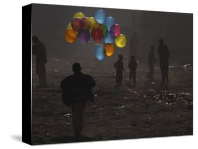Afghan Boy Runs with Balloons to Join His Friends in Dusty Alley in Kabul, Afghanistan