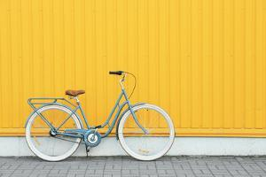 Retro Bicycle near Yellow Wall Outdoors by Africa Studio