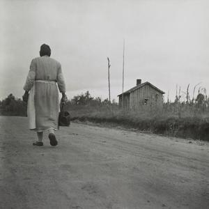 African American Midwife Carrying Her Medical Bag on a Dirt Road in Georgia