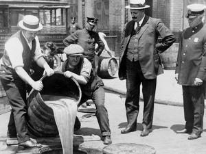 Agents pour liquor into sewer following a raid during the height of prohibition, New York, 1921