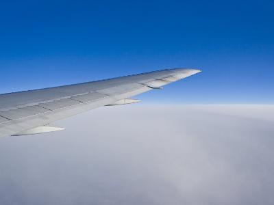 Airplane Just Above Clouds with Sky Split in Blue and White Layers-Mike Theiss-Photographic Print