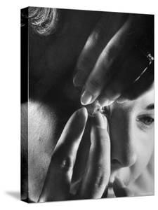 Woman Cautiously Placing a Contact Lens in Her Eye by Al Fenn