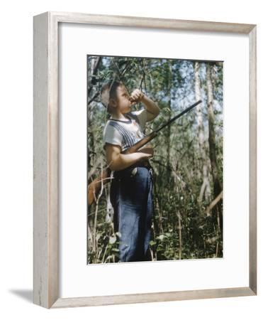 Young Hunter Blowing a Duck Decal Wistle while Holding His Rifle under His Arm
