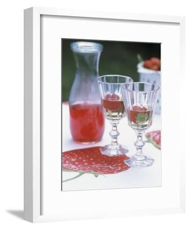 Two Glasses of Strawberry Wine on a Table in the Garden