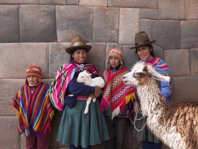 South America, Peru, Cusco. Quechua People in Front of An Inca Wall, Holding a Lamb and a Llama
