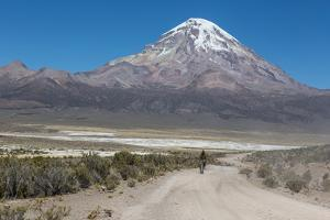 A Man Cycles in the Shadow of Sajama Volcano in Sajama National Park by Alex Saberi
