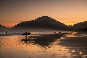 A Surfer Makes His Way Out of the Water at Sunset on Praia Do Itamambuca in Brazil by Alex Saberi