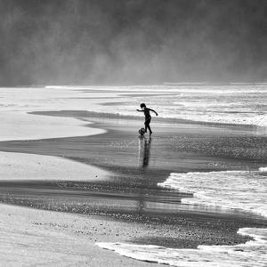 A Young Boy Kicks a Ball on Itamambuca Beach in Ubatuba, Brazil by Alex Saberi