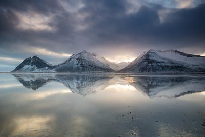 Reflection of mountains on ocean at sunset in Vatnajokull National Park in eastern Iceland