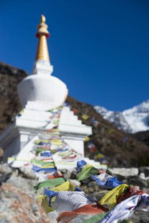 Prayer Flags Adorning a Stupa Flutter in the Wind in the Langtang Valley, Nepal by Alex Treadway