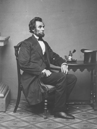 Abraham Lincoln, full-length portrait, seated, 1861