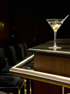 A Martini with an Olive on a Bar by Alexandre Oliveira