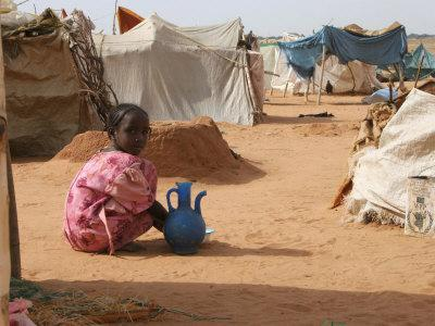 A Girl Washes Plates for Her Family in the North Darfur Refugee Camp of El Sallam October 4, 2006