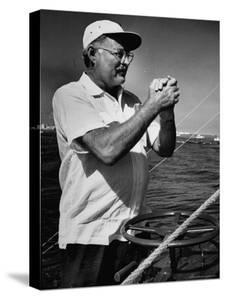 Author Ernest Hemingway at Wheel of Fishing Boat During Fishing Tournament by Alfred Eisenstaedt