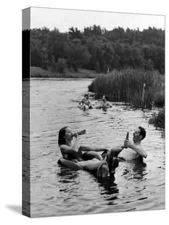 Couple Drinking Beer at Inner Tube Floating Party on the Apple River