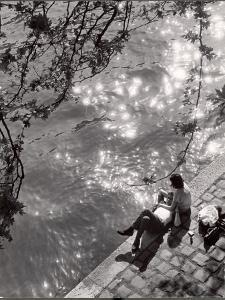 Couple Relaxing on Bank of Seine Near Notre Dame Cathedral During Lunch Hour by Alfred Eisenstaedt