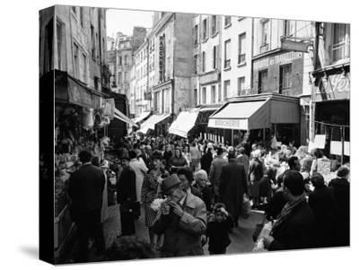 Crowded Parisan Street, Prob. Rue Mouffetard, Filled with Small Shops and Many Shoppers