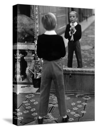English Boy Using Reflection in Mirror in Foyer of Grand Hotel to Fix His Tie