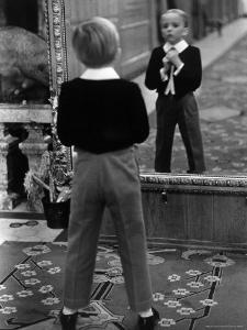 English Boy Using Reflection in Mirror in Foyer of Grand Hotel to Fix His Tie by Alfred Eisenstaedt