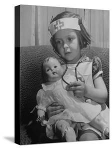 Evelyn Mott playing Nurse with doll as parents adjust children to abnormal conditions in wartime by Alfred Eisenstaedt