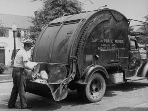 Garbage Man Emptying Trash into Back of Garbage Truck by Alfred Eisenstaedt