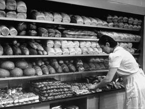 Good of Worker in Bakery Standing in Front of Shelves of Various Kinds of Breads and Rolls by Alfred Eisenstaedt